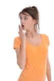 Shocked aisló a la mujer bastante joven sobre blanco. Imagen de archivo