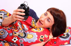Shocked and amazed woman looking at ringing alarm clock Royalty Free Stock Photos