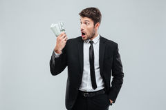 Shocked amazed young businessman standing and holding money. Over white background Stock Photos