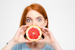 Shocked amusing lady holding grapefruit half in front of mouth Royalty Free Stock Photos