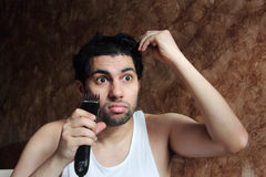 Shocked angry arab young man cutting hair with hair clipper royalty free stock photos