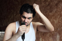 Shocked angry arab young man cutting hair with hair clipper stock photos