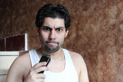 Shocked angry arab young man cutting hair with hair clipper royalty free stock photography