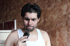 Shocked angry arab young man cutting hair with hair clipper stock photography