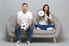 Shocked angry couple woman man football fans in white t-shirt cheer up support favorite team with soccer ball, holding royalty free stock photo
