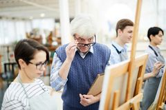 Shocked Art Teacher Looking at Painting. Portrait of mature art teacher criticizing work of student painting picture on easel in art class, copy space royalty free stock photos