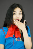 Shocked Asian air stewardess with hand over mouth Royalty Free Stock Photo