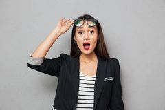 Shocked asian business woman holding eyeglasses and looking at camera. Shocked asian business woman holding eyeglasses and looking at the camera over gray stock photos
