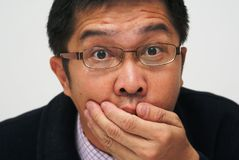 Shocked asian businessman. Surprised expression on asian chinese businessman covering mouth Stock Images