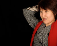 Shocked Asian woman. Half body portrait of shocked Asian woman raising hand over head, isolated on black background Royalty Free Stock Image