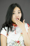 Shocked Asian woman with hand over mouth  on colored background Royalty Free Stock Photo