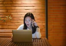 Shocked Asian woman using laptop at night, freelance working lat royalty free stock image