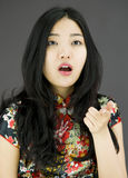 Shocked Asian young woman with pointing  on colored background Stock Photo