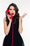 Shocked astonished beautiful retro styled woman talking on red telephone Royalty Free Stock Image