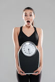 Shocked astonished young woman athlete holding weighing scale Royalty Free Stock Image