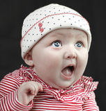 Shocked baby blue eyes. Baby girl looks up shocked with big blue eyes stock photo