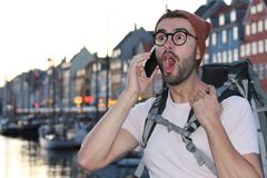 Shocked backpacker getting good news during phone call.  Stock Photos