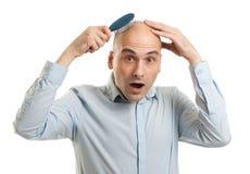 Shocked bald man. Holding comb Stock Image