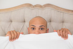 Shocked bald man covering face with sheet in bed Stock Images