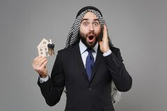 Shocked bearded arabian muslim businessman in keffiyeh kafiya ring igal agal classic black suit tie  on gray
