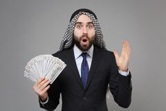 Shocked bearded arabian muslim businessman in keffiyeh kafiya ring igal agal suit isolated on gray background