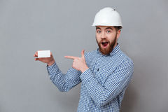 Shocked bearded builder holding copyspace business card. Image of shocked bearded builder holding copyspace business card and pointing standing over grey Stock Images