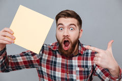 Shocked bearded man holding copyspace blank. Picture of shocked bearded man holding copyspace blank standing over grey background and pointing Stock Image