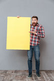 Shocked bearded man holding copyspace board and pointing. Picture of shocked bearded man holding copyspace board and pointing standing over grey background Stock Image