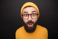 Amazed bearded man in yellow hat. Shocked bearded man wearing glasses and yellow clothes on black background Royalty Free Stock Photos