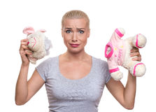 Shocked beautiful blonde woman with damaged teddy bear. expressi Royalty Free Stock Images