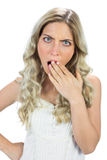 Shocked blond model hiding her mouth wide open Royalty Free Stock Photos