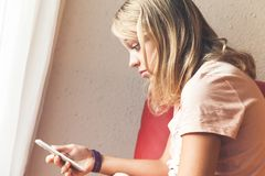 Shocked blond teenage girl with smartphone royalty free stock images