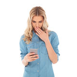 Shocked blonde woman is reading messages on her smartphone Stock Photo