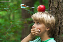 Shocked boy. With apple on his head, and arrow shot through Royalty Free Stock Image
