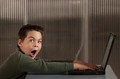 Shocked boy with a laptop computer Royalty Free Stock Image