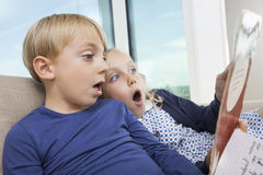 Shocked brother and sister reading storybook at home Stock Image