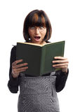 Shocked brunette schoolgirl looking in the book. Holding in her hands over white background Stock Photos