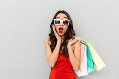 Shocked brunette woman in casual clothes and sunglasses holding packages. While touching her cheek and looking at the camera with open mouth over grey Stock Images
