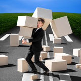 Shocked business man carrying carton boxes that fall down to the Royalty Free Stock Photography