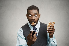 Shocked business Man reading breaking news on Phone while eating. Closeup portrait surprised funny looking corporate business man holding, reading bad news on Royalty Free Stock Photography
