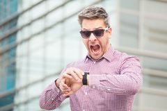 Shocked business person while checking time on his watch outdoors. stock photos