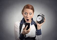 Shocked business woman with alarm clock looking at smart phone Royalty Free Stock Photo