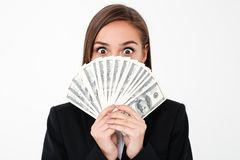 Shocked business woman covering face holding money. Photo of shocked business woman standing isolated over white background covering face holding money. Looking Stock Photo