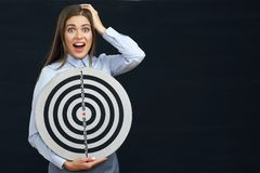Shocked business woman holding target. Black background Stock Image