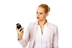 Shocked business woman looking at alarm clock Royalty Free Stock Photography