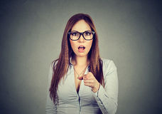 Shocked business woman looking surprised pointing finger at camera Royalty Free Stock Photography