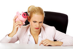 Shocked business woman sitting behind the desk and listen too her piggybank Stock Photography