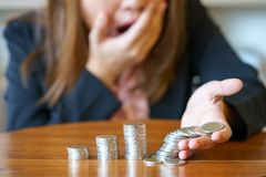 Shocked business woman with stack coins - stock and market down. stock photos