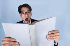 Shocked businessman. Reading a book shot in studio over blue background Stock Photos