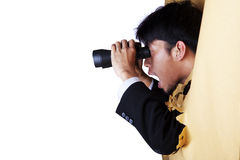 Shocked businessman with binoculars. Shocked businessman breaking through a paper wall looking through binoculars Royalty Free Stock Images